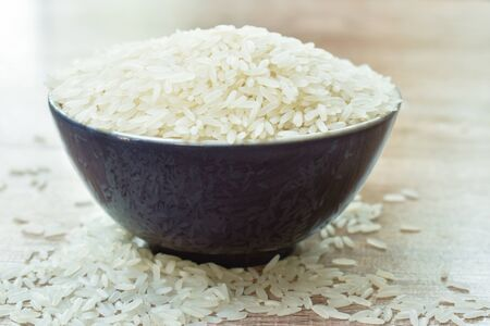 Thai jasmine rice paddy in bowl on wooden table