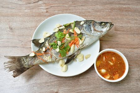 steamed bass fish with garlic dipping spicy sauce on table Stock Photo