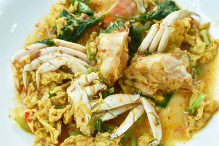 stir fried swimmer crab in yellow curry and egg on plate