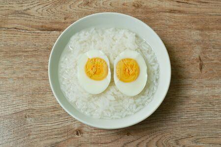 boiled egg half cut topping rice porridge in bowl on table Stock Photo