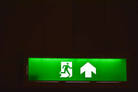 green electric light box sign fire exir door on wall in building Фото со стока