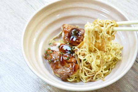 Chinese egg noodles roasted chicken dressing Teriyaki Japanese sauce picking by plastic chopsticks on bowl