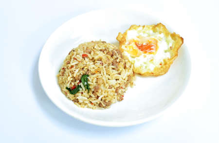 spicy stir fried chop pork with chili and basil leaf mixed rice topping egg on plate