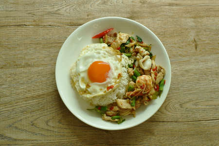 spicy fried seafood and meat chili and herb on rice topping egg in plate
