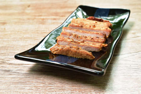fried slice salty pork sirloin with garlic and pepper on plate Фото со стока