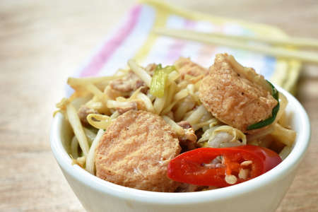 fried bean sprout with slice egg tofu and chop pork in cup eat by chopsticks on table