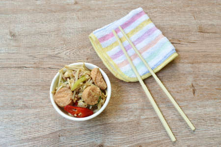 fried bean sprout with slice egg tofu and chop pork in cup on table