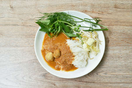 rice noodles dressing with meat ball fish coconut milk curry sauce and fresh vegetable on plate