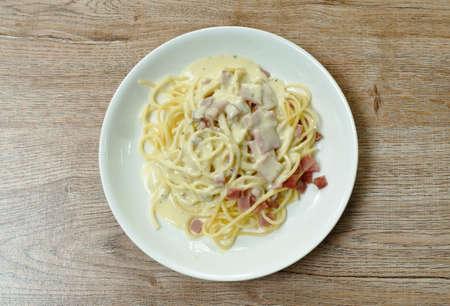 spaghetti white cream sauce topping slice ham pork on plate