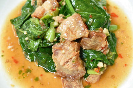 spicy fried Chinese kale with slice crispy pork in soybean and oyster sauce on plate Фото со стока