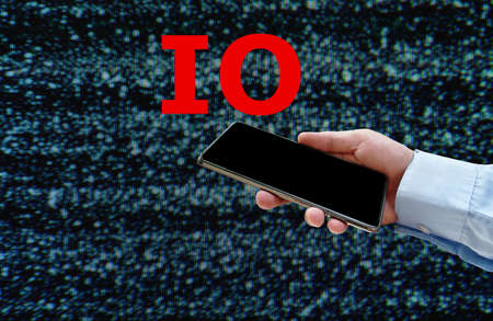 red letter IO or information operation over smart phone in businessman hand on glith background