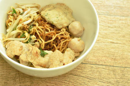 dry yellow egg noodles topping slice boiled pork and meat ball in bowl on table