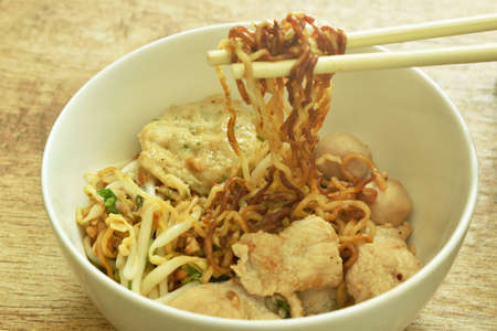 chopsticks picking dry yellow egg noodles topping slice boiled pork and meat ball in bowl on table Foto de archivo