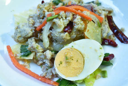 boiled egg half cutting topping sour and spicy minced pork salad on plate Banco de Imagens