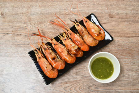 grilled river shrimp arranging on plate dipping spicy sauce