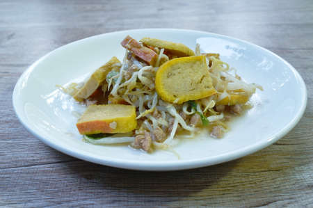 fried bean sprout with slice yellow tofu and chop pork in plate on table