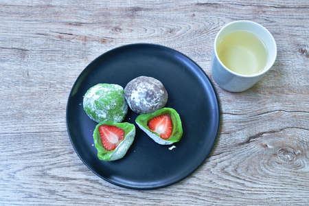 Daifuku stuffed fresh strawberry Japanese sweet made from flour and bean on plate eat couple hot tea cup