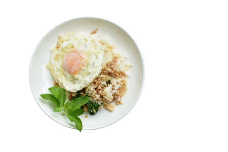 spicy fried chop pork with basilleaf and chili topping egg on rice in dish