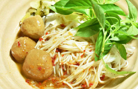 rice noodles dressing with meat ball fish coconut milk curry sauce and fresh vegetable on bowl