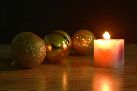 golden ball couple candle light for decoration in Christmas and new year festival in black background