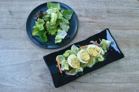 boiled egg half cutting tin sour and spicy salad on plate with fresh vegetable Banque d'images
