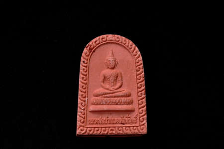 small Buddha image amulet carrying for luck and  remember to do good thing on black background foreign language is named of Buddha is Luang Por Pakdand mean buddha with red lips