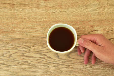 hand  holding black coffee cup on table
