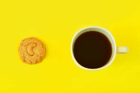 chew nut cookie and black coffee cup on yellow background