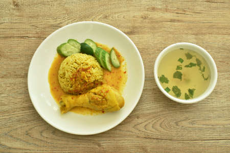 rice cooked with chicken in curry on plate and soup cup
