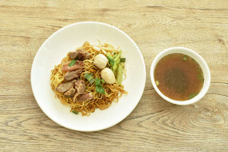 Chinese yellow egg noodles topping braised pork and ball on plate with bone in brown herb soup cup Banque d'images