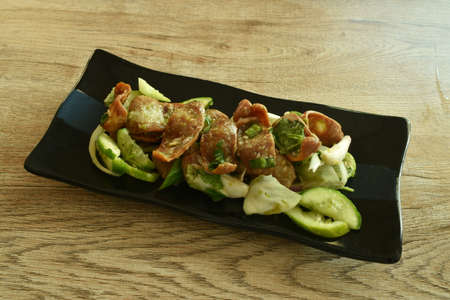 spicy slice fried Chinese pork sausage with cucumber and shallot Thai salad eat couple fresh vegetable on plate