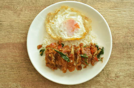 spicy fried crispy chicken with basil leaf and chilli topping egg on rice in plate Banque d'images