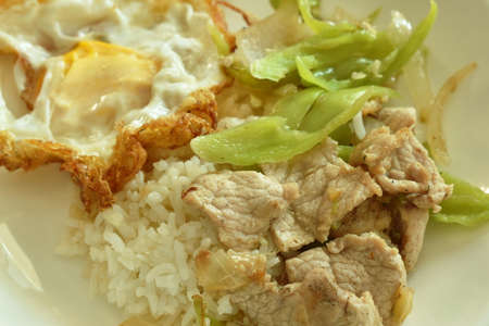 stir fried pork with slice sweet long pepper and onion topping rice couple on plate