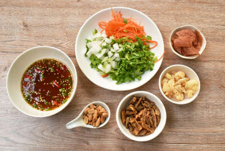 ingredient of crispy fish with pork couple maw topping peanut in spicy and sour chili sauce salad on plate