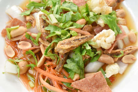 crispy fish with pork couple maw topping peanut in spicy and sour chili sauce salad on plate