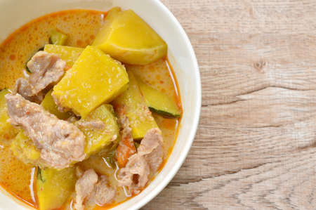 spicy boiled pumpkin with slice pork in curry on bowl