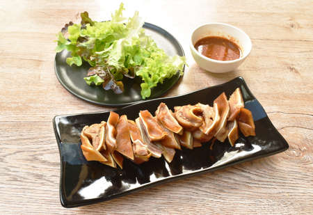 grilled pork ear slice dipping spict chili sauce eat couple fresh vegetable on plate