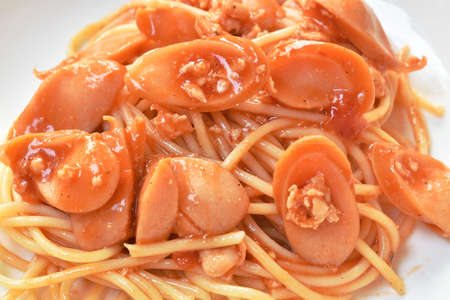 fried spaghetti topping slice sausage with chop pork and ketchup on plate