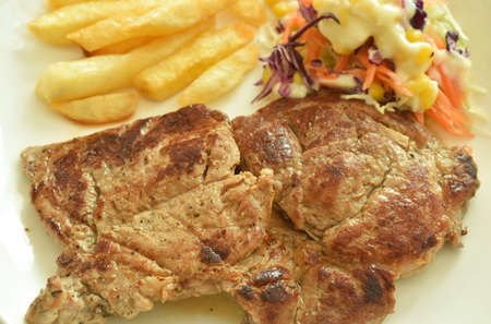 grilled pork neck steak with french fries and salad dressing mayonnaise on plate dipping spicy sauce