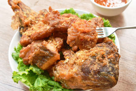 batter fried slice mango or red Tilapia fish with chop garlic stabbing by silver fork dipping spicy sauce