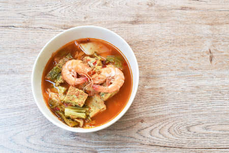 fried egg stuffed climbing wattle and shrimp with vegetable in spicy sour soup on bowl