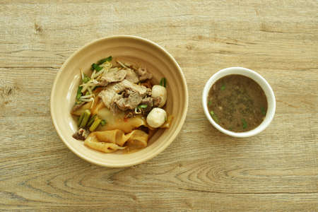 dry large rice noodles topping slice braised and fermenting with meatball dressing black sweet soy sauce on bowl eat couple brown herb soup Stockfoto