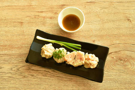 steamed Chinese dumpling stabbing minced pork and shrimp or dim sum dipping soy sauce on plate