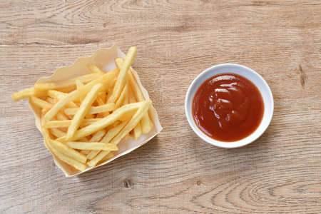 French fries mixed with salt in paper box dipping ketchup on table