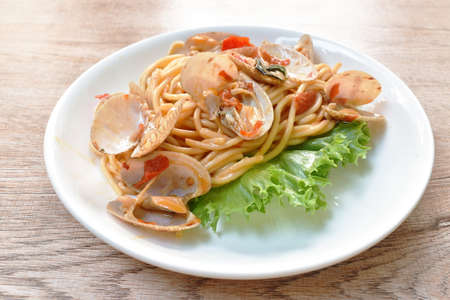 spicy stir fried spaghetti clams with pepper and basil leaf on plate