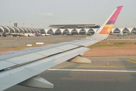 Bangkok Thailand March 27, 2021 : wing on commercial plane take off from Suvarnabhumi airport
