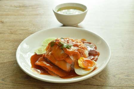 roasted pork slice topping on plain rice dressing sweet red gravy sauce on plate