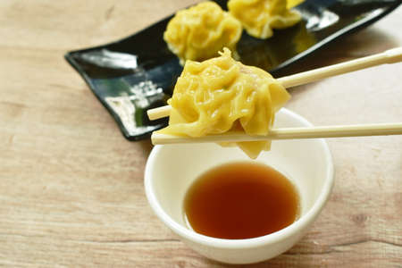steamed Chinese dumpling stuffed mashed pork dipping soy sauce on plate