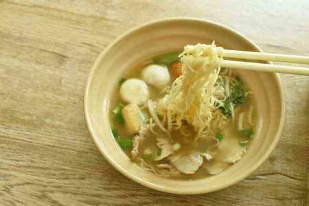 Chinese egg yellow noodles topping slice boiled pork and ball with soup picking by chopsticks in bowl Imagens