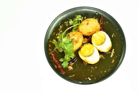 fried egg half cut dressing sweet tamarind sauce topping chili on plate